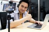 Young asian male gamer casting and broadcasting his online playing video game using smart mobile pho poster