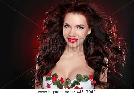 Red Lips. Portrait Of Sexy Brunette Girl With Professional Make-up And Hairstyle Over Dark Backgroun