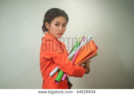 Busy Asian Business Woman With A Lot Of Folders And Colorful Papers On Background .