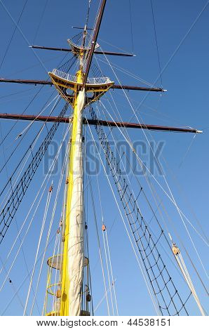 Mainmast of big sailboat with blue sky in background