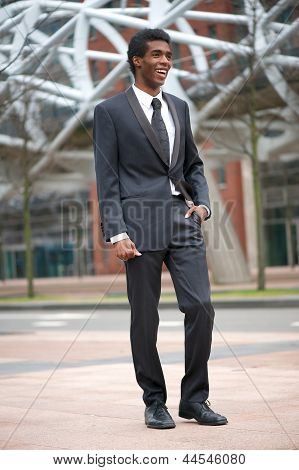 Portrait Of A Smiling African American Businessman Walking In The City