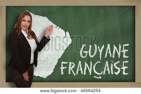 Teacher Showing Map Of French Guiana On Blackboard