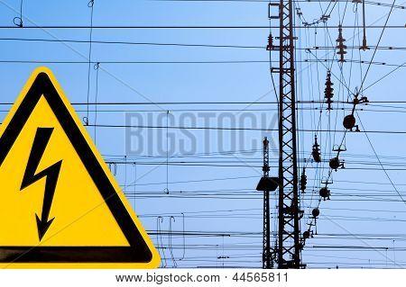 Hohe Spannung-Zeichen und Eisenbahn obenliegende Verdrahtung