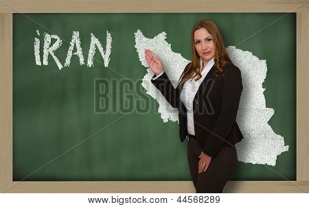 Teacher Showing Map Of Iran On Blackboard