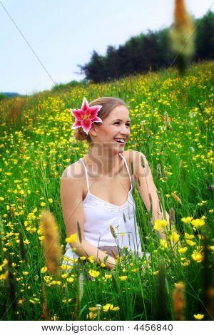 Frau mit einer Blume im Haar auf einer Wiese