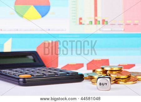 Dices Cube With The Word Buy, Golden Coins, Calculator And Financial Diagrams As Background. Selecti
