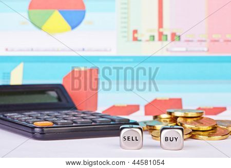 Dices Cubes With The Words Buy Sell, Golden Coins, Calculator And Financial Diagrams As Background.