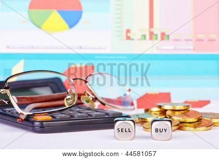 Dices Cubes With The Words Buy Sell, Golden Coins, Calculator,glasses  And Financial Diagrams As Bac