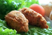 picture of pasteis  - Portuguese fish cakes known as Pasteis de Bacalhau on green lettuce with tomato in the background shallow depth of field