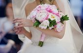 stock photo of bridal veil  - Bride in a white dress touching the ring and holding her wedding peonies bouquet - JPG