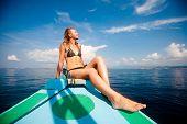 stock photo of bimbo  - Young sexy woman in bikini enjoying the sun on the boat - JPG