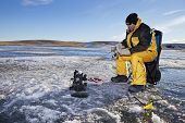 stock photo of ice fishing  - Man ice fishing on a frozen Canadian lake - JPG