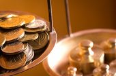 stock photo of copper coins  - vintage scale wheights outweigh coins on an old balance - JPG
