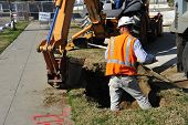 stock photo of power-shovel  - In spite of power equipment hand digging is still required on this construction project - JPG