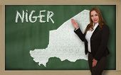 Teacher Showing Map Of Niger On Blackboard