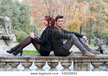Elegant Couple Sitting Back To Back On Stone Balusters