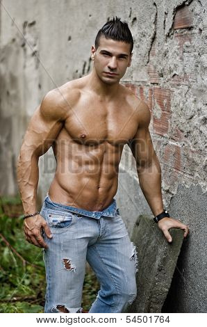 Muscular Young Latino Man Shirtless In Jeans Leaning On Wall