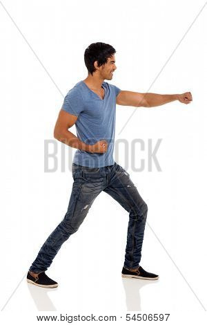 side view of indian man doing karate in casual clothes