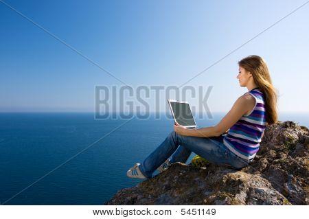Mujer con ordenador portátil y mar
