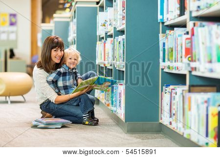 Portrait of happy boy and teacher reading book by bookshelf in library