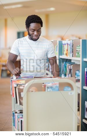 Smiling male librarian with trolley of books standing by shelves in library