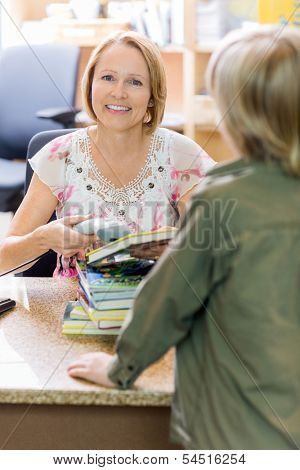 Portrait of happy mature librarian scanning books while boy standing at checkout counter in library