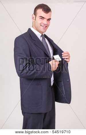 Smiling businessman takes a business card out of his jacket