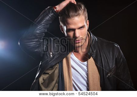 young fashion man passing his hand through his hair on dark background