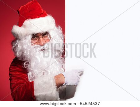 santa claus is presenting a blank board by pointing his finger on red background