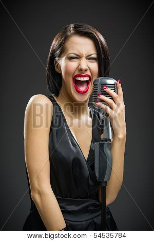 Half-length portrait of shouting female singer wearing black evening dress and keeping microphone on grey background. Concept of music and retro fashion