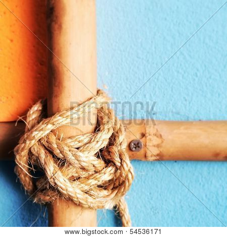 Cross bamboo bars with rope tied on the vintage wall background.