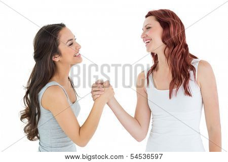 Two cheerful young female friends arm wrestling against white background
