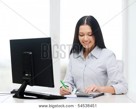 business, education, technology and tax concept - smiling businesswoman or student with coputer, calculator, notebook and pen