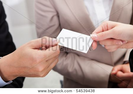 Businesspeople Exchanging Cards Over Coffee