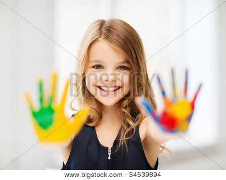 education, school, art and painitng concept - smiling little student girl showing painted hands at school