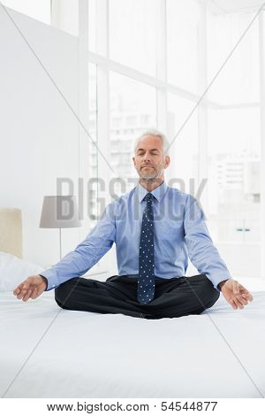 Full length of a relaxed mature businessman sitting in lotus posture on bed at home
