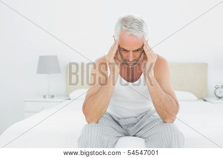 Mature man suffering from headache in bed at home
