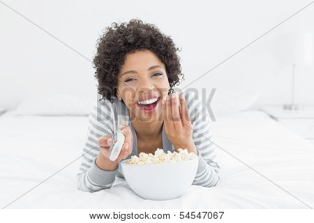 Portrait of a cheerful young woman with remote control and popcorn bowl lying in bed at home