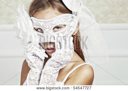 Portrait of a fashion girl wearing wedding dress and venetian mask