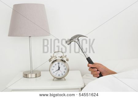 Close-up of a man's hand smashing alarm clock with hammer in bed at home