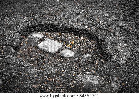 Tarmac road with big holes in Belgium