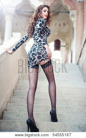 Fashion pretty young woman with long legs climbing old stone stairs. Beautiful long hair brunette