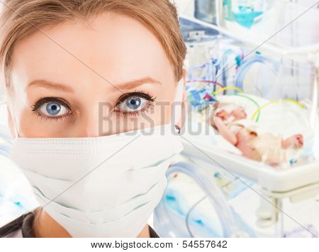Young female doctor in intensive care unit with newborn child