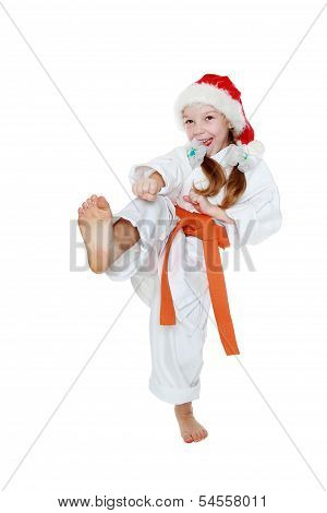 On a white background little girl in a kimono hits a kick leg insulated