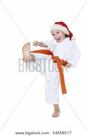 With the orange belt and cap of Santa Claus girl beats a kick leg
