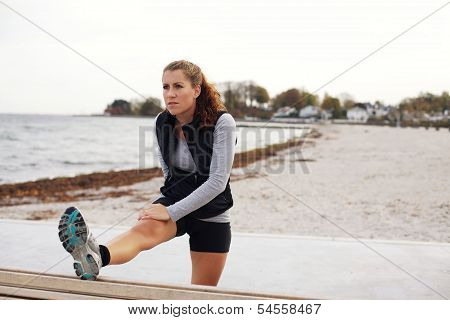 Healthy Woman Stretching After Workout On Beach