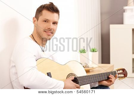 Portrait of young goodlooking guitarist, playing guitar at home.
