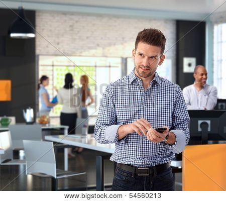 Casual businessman using mobile phone at modern stylish office, smiling.