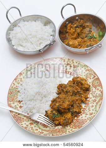Methi murgh - chicken cooked with fresh fenugreek leaves -  served on a plate with rice with the curry sauce  behind, in a kadai, or karahi, traditional Indian wok,  next to a bowl of basmati rice