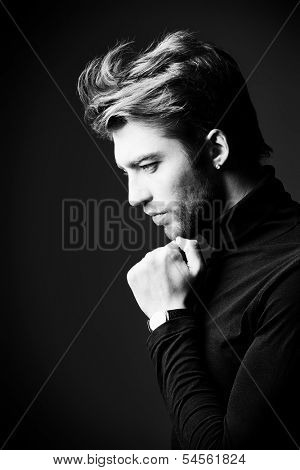 Imposing man in elegant black clothes posing over dark background. Profile portrait.